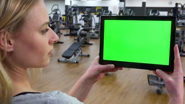 Thumbnail for A Young Beautiful Woman Looks at a Tablet with a Green Screen in a Gym - Closeup From Behind