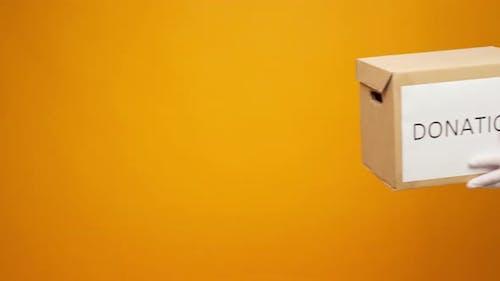 Menschliche Hände halten Karton mit Coronavirus-Spenden vor gelbem Hintergrund