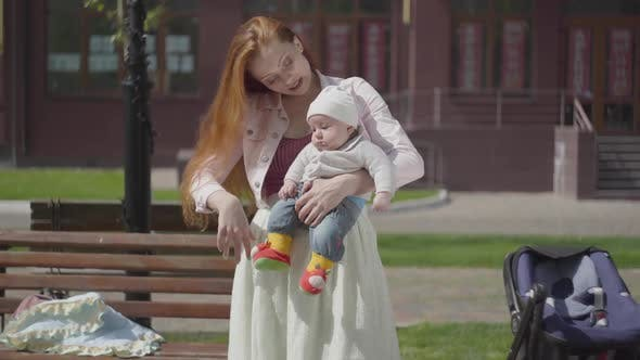 Thumbnail for Portrait Pretty Red-haired Woman Playing with Her Child Sitting on the Bench. The Stroller Standing