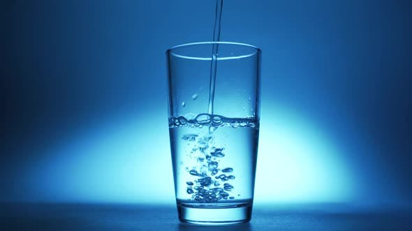 Pure Clear Water Is Poured Into a Glass on a Blue Background.