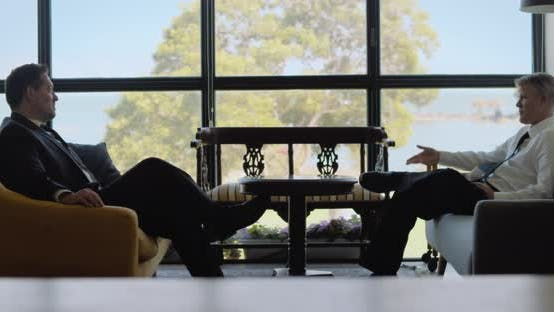 Two businessmen talking to each other while sitting in comfort sofas near a window, having a meeting