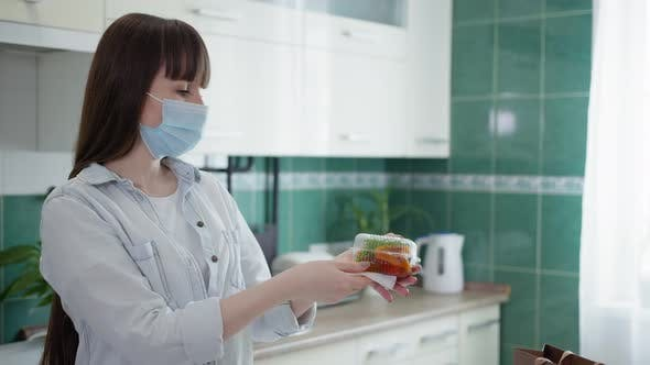 Food Processing, Adult Girl in Medical Mask Observes Precautions and Disinfects Containers with Food