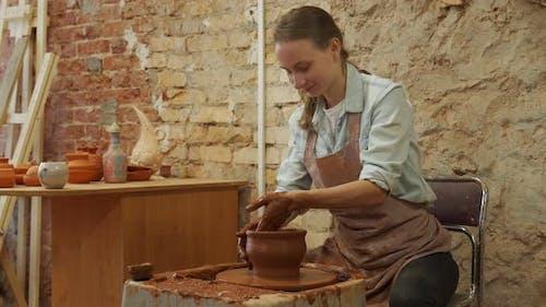 Female Potter Sculpts a Clay Pot