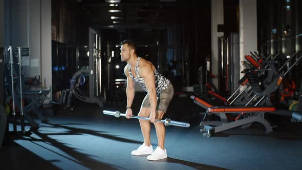 Thumbnail for Athletic Man Trains His Hands and Shoulders With Barbell Weight