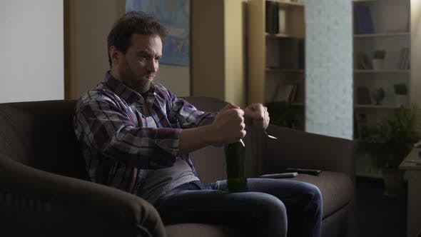 Thumbnail for Man Sitting on Couch in Dark Room, Trying to Open Beer Bottle with Fork, Despair