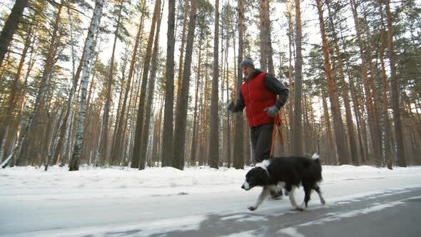 Thumbnail for Man Running with Dog on Winter Day