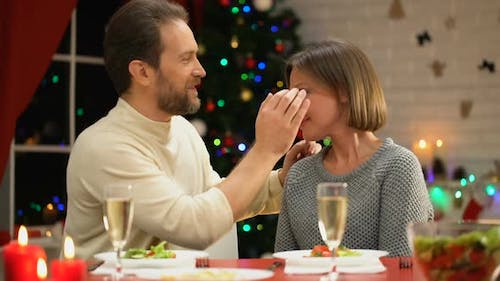 Mid-Aged Man Tenderly Kissing Wife on Christmas Eve