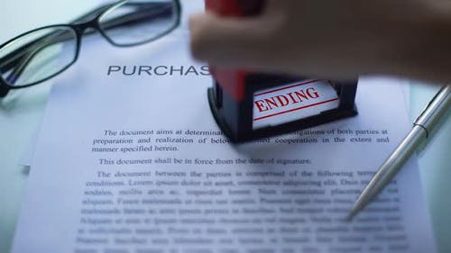 Purchase Agreement Pending Officials Hand Stamping Seal on Business Document