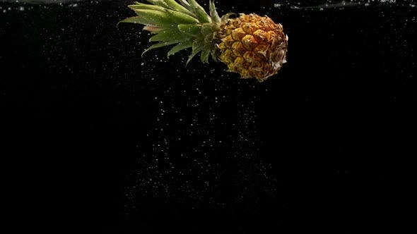 Thumbnail for Tropical Fruit Pineapple Rotating and Falling Into Water with Splash Bubbles on Black Background
