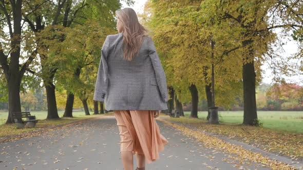 Thumbnail for Back View of a Slim Caucasian Woman in Checkered Jacket and Mustard Dress Walking in the Autumn Park