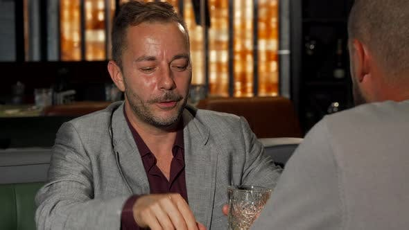 Thumbnail for Mature Man Telling His Friend Something Expressively While Having Drinks