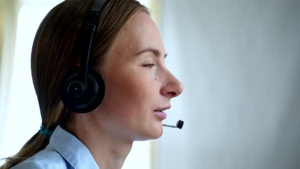 Customer Support Agent or Call Center with Headset Works on Desktop Computer While Supporting the