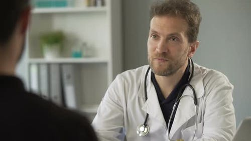 Male Therapist Chatting With Patient at Hospital, Healthcare and Medicine