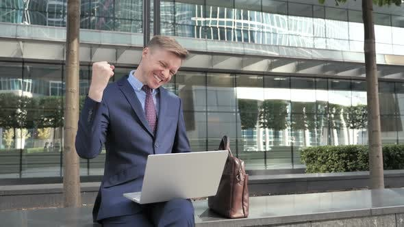 Thumbnail for Businessman Celebrating Results on Laptop Sitting Outside Office