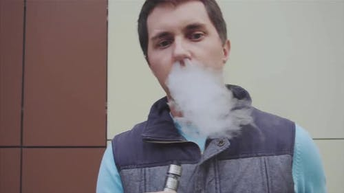 Young Vaper Man Exhaling Big Clouds of Smoke with Ecigarette Vape Slow Motion