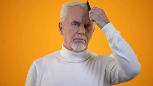 Male Pensioner Combing Gray Hair, Looking Shockingly at Hairbrush, Trichology