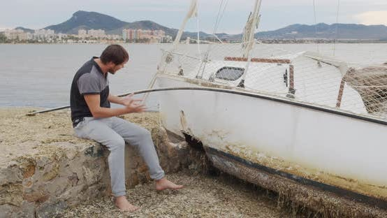 Thumbnail for The Man Sits in Despair Near His Yacht Broken After a Storm.