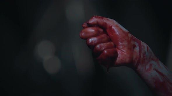 Personne possédée tenant un morceau de verre dans la main sanglante, cauchemar et horreur