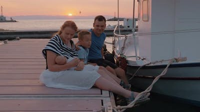 Parents with Elder Son and Baby Sitting on the Pier at Sunset