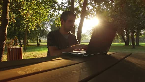 Thumbnail for Man Working on the Computer in the Park at Sunset