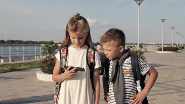 Thumbnail for School Friends Boy and Girl Walking and Looking Into Smartphone