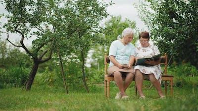 Elder Sister Women View Photos in Old Family Album