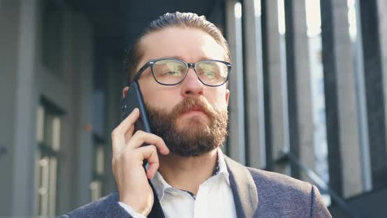 Thumbnail for Bearded Businessman in Glasses which Talking on Mobile with Business Partner Outdoors