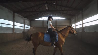 Young Woman Gets on a Horse and Riding a Horse in a Covered Hangar, Female Trains Riding on a Horse.