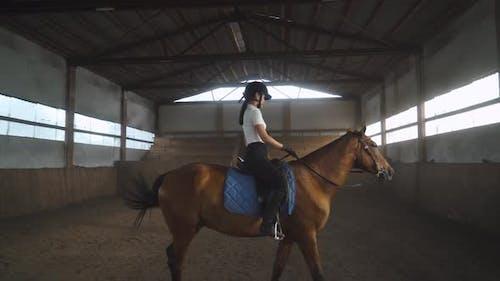 Junge Frau steigt auf ein Pferd und reitet auf einem Pferd in einem überdachten Hangar, weibliche Züge reitet auf einem Pferd.