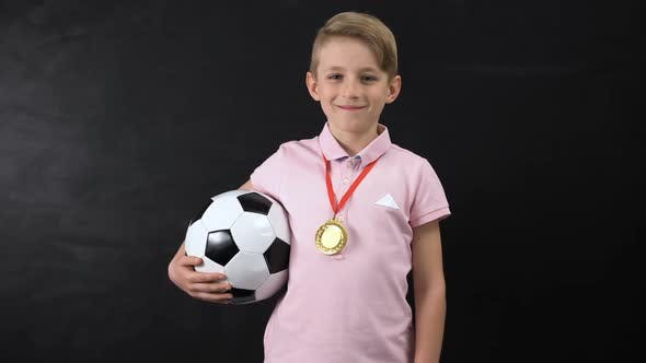 Boy With Ball and Medal Standing Near Blackboard, Football Competition Winner