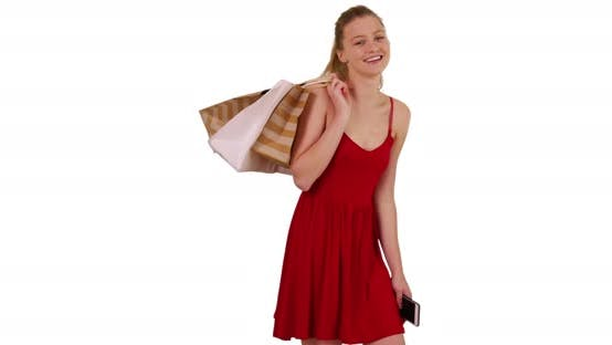 Woman holding shopping bags over shoulder on white background with copy space