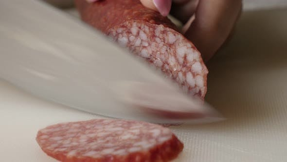 Thumbnail for Cutting cured sausage of air-dried meat close-up 4K 2160p 30fps UltraHD footage - Salami cut on smal