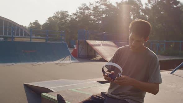 Skater Listening to Music in Skatepark and Relaxing