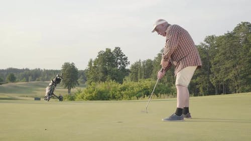 Mature Man Playing Golf Alone on the Golf Field. Senior Man Hit the Ball Using Golf Club. The Guy