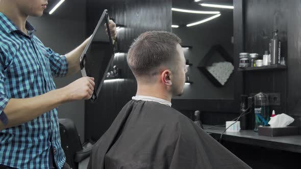 Thumbnail for Barber Holding a Mirror for His Male Client To Check Out New Haircut