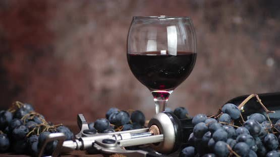 A Glass of Wine with Fresh Grapes Slowly Rotates. On Rustic Background.