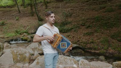 boy plays the accordion in the mountains