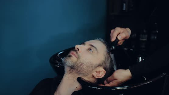 Man with Gray Hair Washes His Hair in the Salon Before Cutting