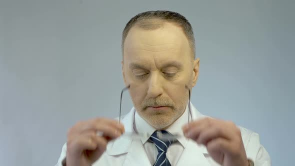 Thumbnail for Chief Physician Putting on Glasses, Ready to Examine Patient, Looking at Camera
