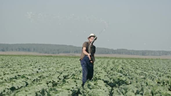 Farmer Splashing Water from Hose before Camera