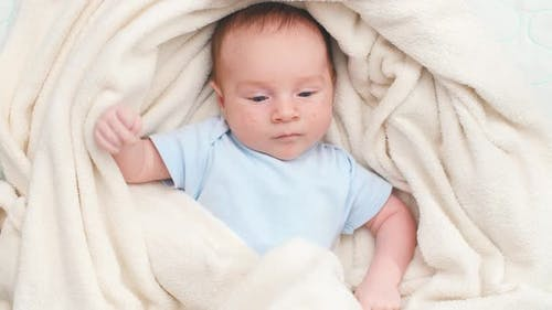 Above View on Adorable Newborn Baby Covered in Soft Blanket Lying in Crib
