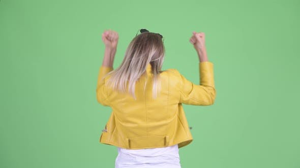 Thumbnail for Rear View of Happy Young Rebellious Blonde Woman with Fists Raised