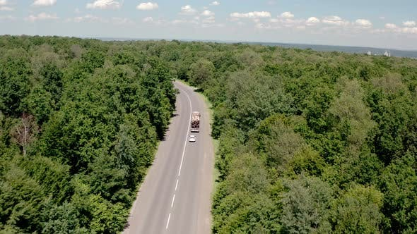 Thumbnail for Aerial View of White Truck with Cargo Semi Trailer and Several Cars Moving on Road in the Forest. V4