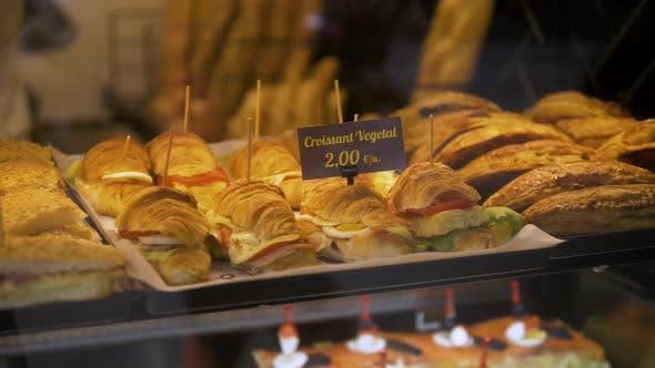 Thumbnail for Anzeige von vielen großen Sandwiches hinter Glasfenster von Laden gefüllt mit Schinken, Käse und Gurken