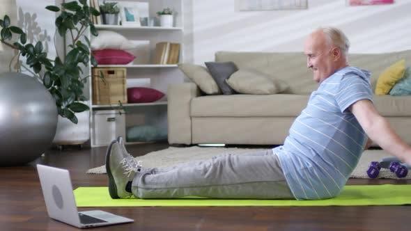 Senior Man Stretching auf Matte und Video Workout ansehen