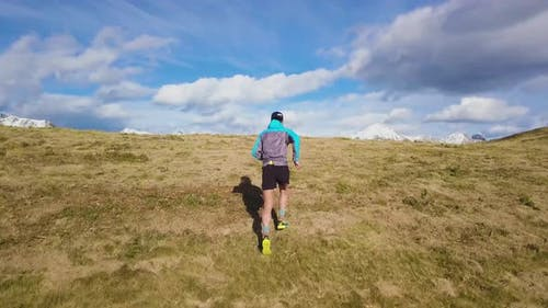 Man Runs Uphill In The Meadow