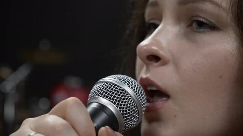 Brunette caucasian woman with beautiful blue eyes is singing emotional song into microphone.
