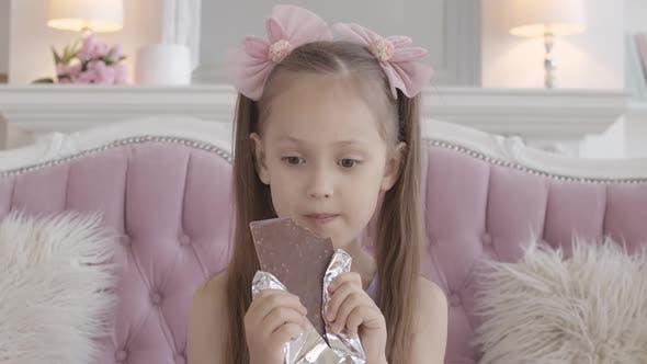 Thumbnail for Portrait of Charming Little Girl Eating Chocolate, Brunette Caucasian Kid Biting Sweet Dessert