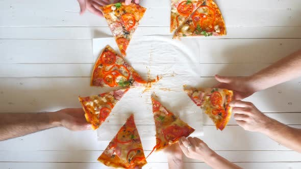 Top View Male and Female Hands Taking Slices of Pizza with Cheese, Tomatoes and Ham From Food