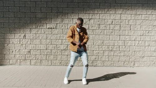 Portrait of Happy Guy Dancing Outside Against Wall Background Performing Street Dance